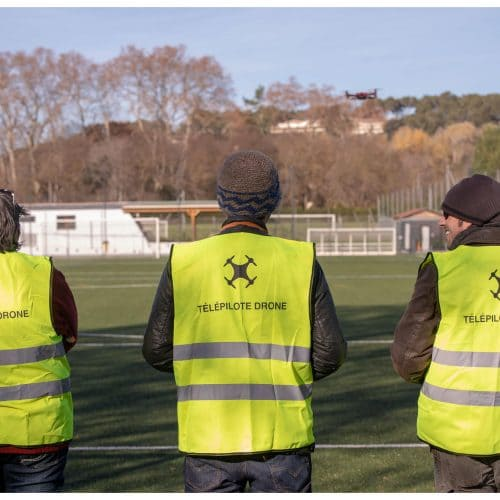 3 élèves avec leurs gilets télépilote drone sur un stade de foot