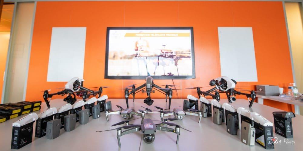 6 drones avec leurs batteries sur une table
