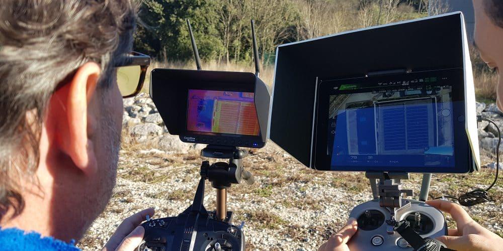 deux personnes qui regardent un retour écran de la prise de vu effectuer par le drone