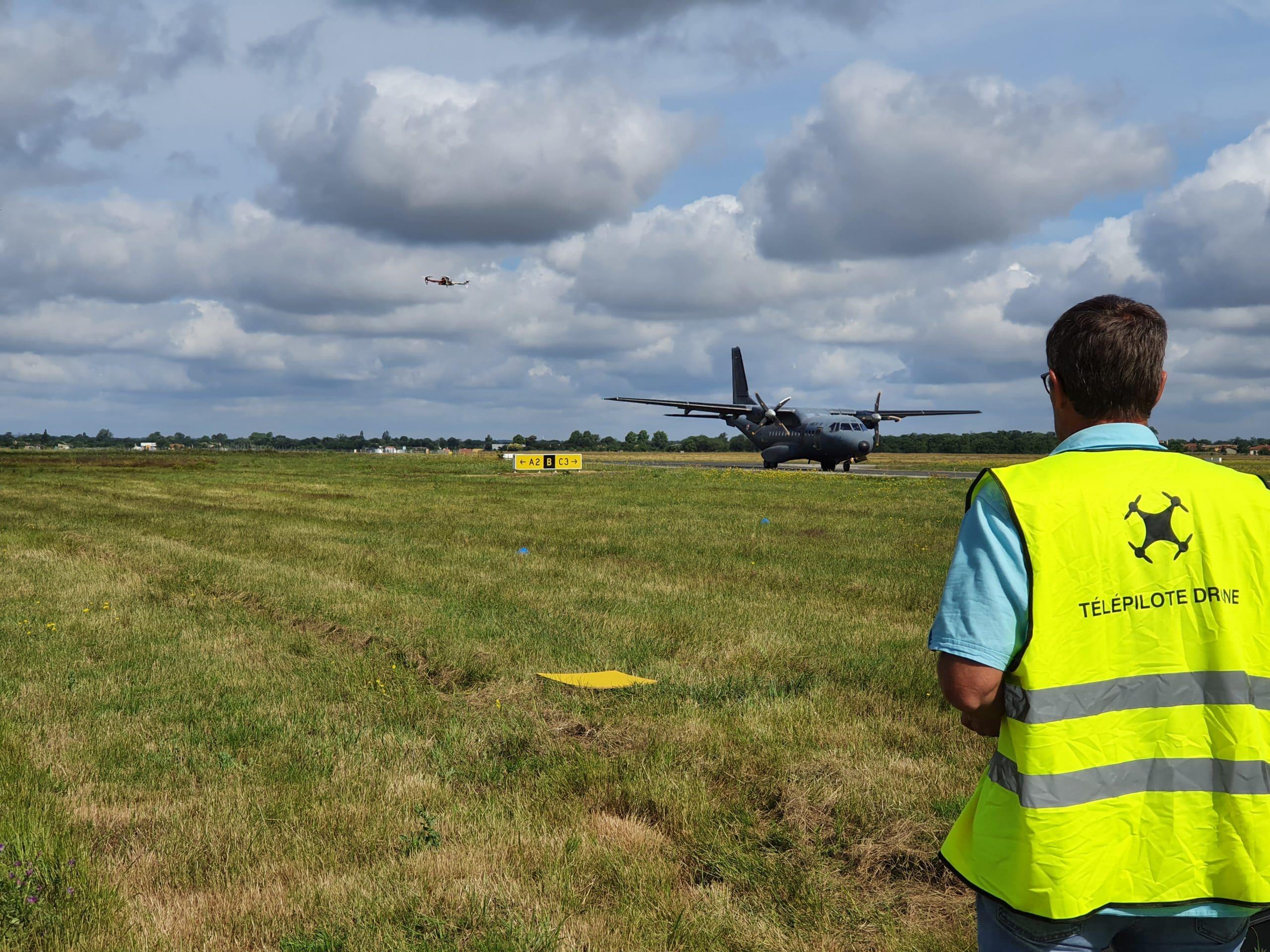 stagiaire qui fait voler son drone sur l'aéroport