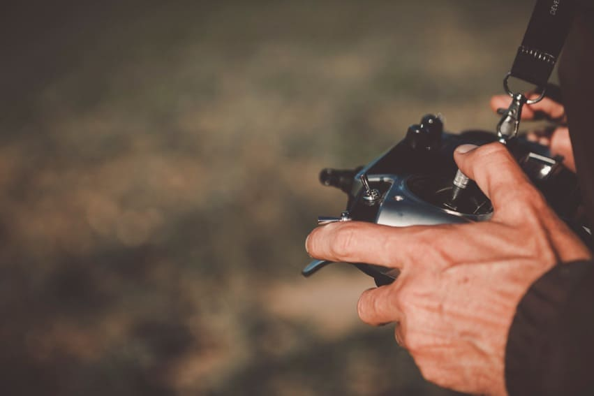 deux mains sur une télécommande de drone